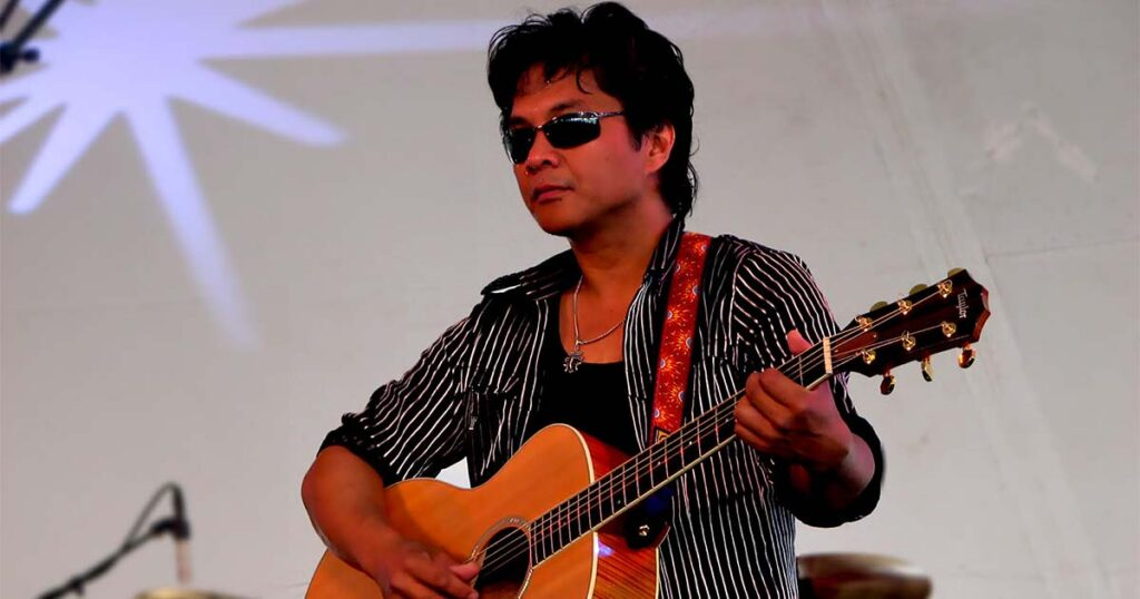Red Reyne playing acoustic guitar